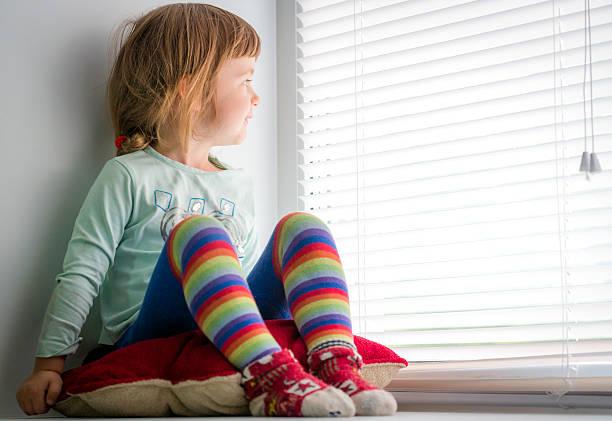 Cтоковое фото Любопытно ребенка выглядывает из окна