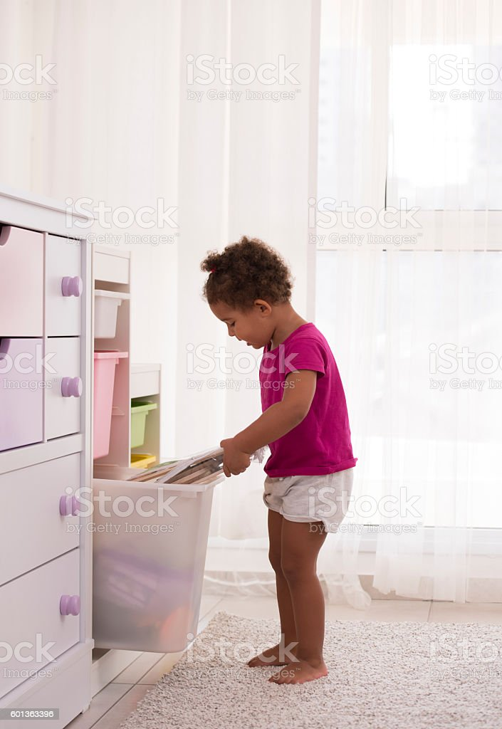 Curious child opening drawer with kid games and books. stock photo