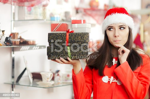 Beautiful funny woman holding a pile of wrapped Christmas gifts