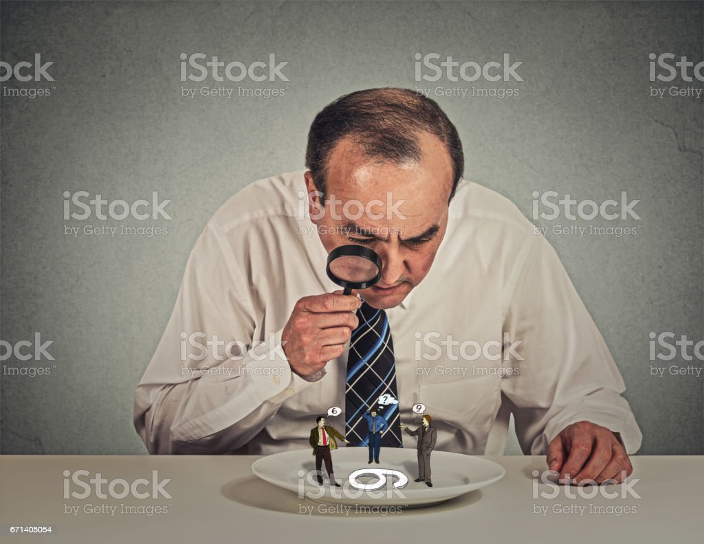 Curious corporate businessman skeptically meeting looking at small employee standing on table plate through magnifying glass stock photo