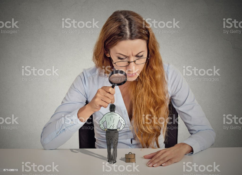 Curious corporate businesswoman skeptically meeting looking at small employee standing on table through magnifying glass stock photo