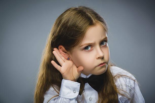 se siente decepcionado niña escucha. retrato de primer plano de un niño auditivas, los padres - ironía fotografías e imágenes de stock