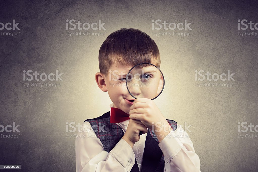 Curious Exploring little boy with magnifying glass stock photo