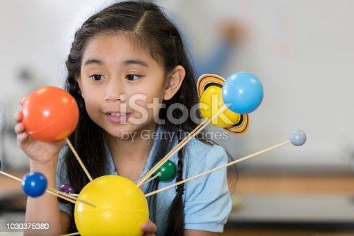 Happy Asian schoolgirl studies model of the solar system.