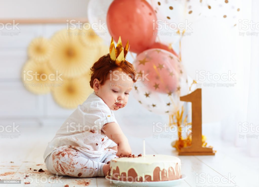 curious funny baby boy poking finger in his first birthday cake stock photo