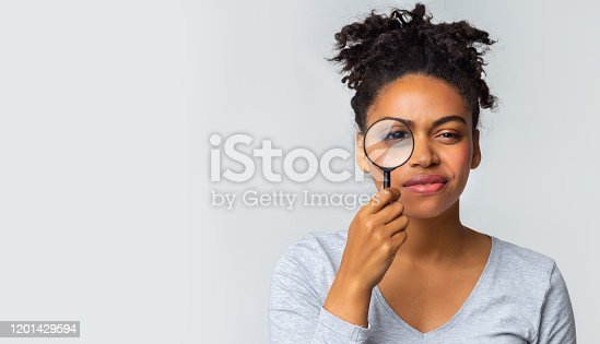istock Curious girl holding magnifier over grey background 1201429594