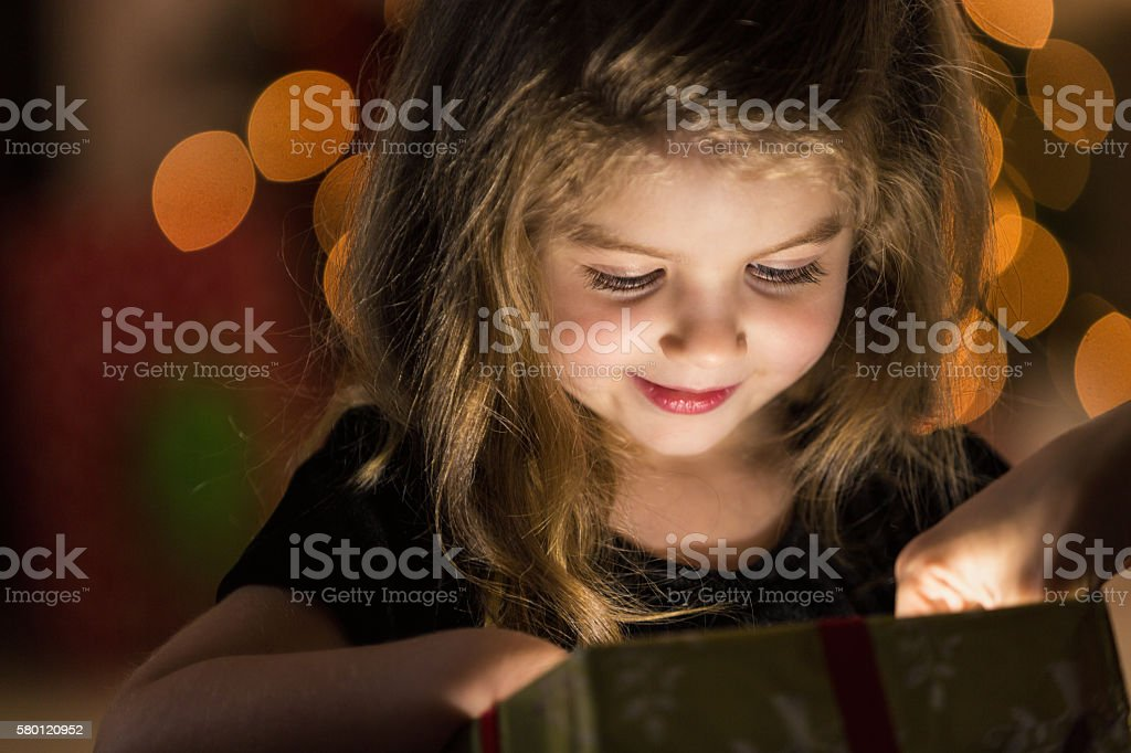 Curious girl peeks inside a Christmas present Beautiful Caucasian little girl smiles as she curiously reaches into a Christmas gift wrapped in gold wrapping paper. A light is shining from the box illuminating her face. She has long blond hair and is wearing a black blouse. Christmas tree lights are blurred in the background. Affectionate Stock Photo