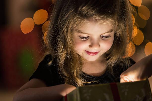 Curious girl peeks inside a Christmas present stock photo