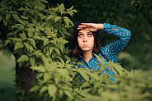 istock Curious Jealous Woman Spying from Bushes 1162235202