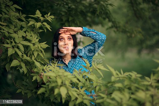 istock Curious Jealous Woman Spying from Bushes 1162235203