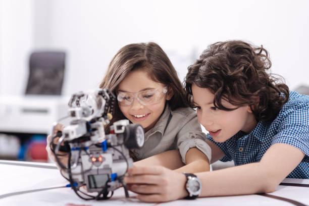 neugierige kinder spielen mit roboter in der schule - lernfortschrittskontrolle stock-fotos und bilder