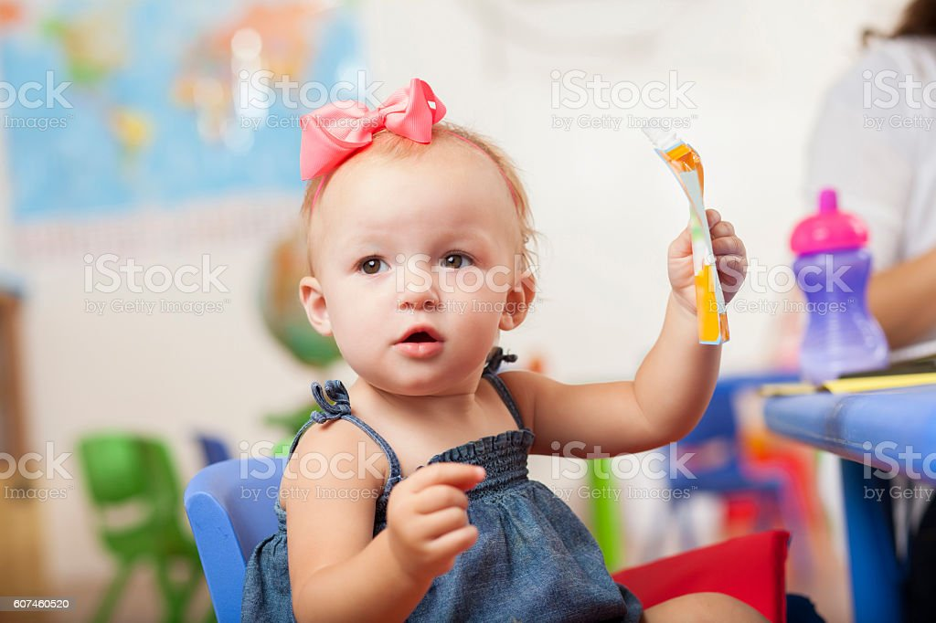 Curious little toddler girl playing at preschool stock photo