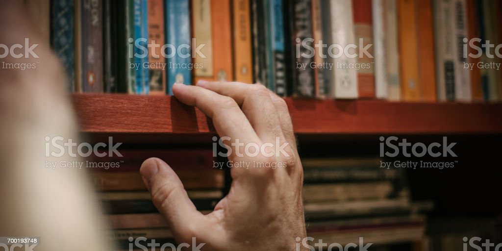 Curious man choosing book in his library at home stock photo