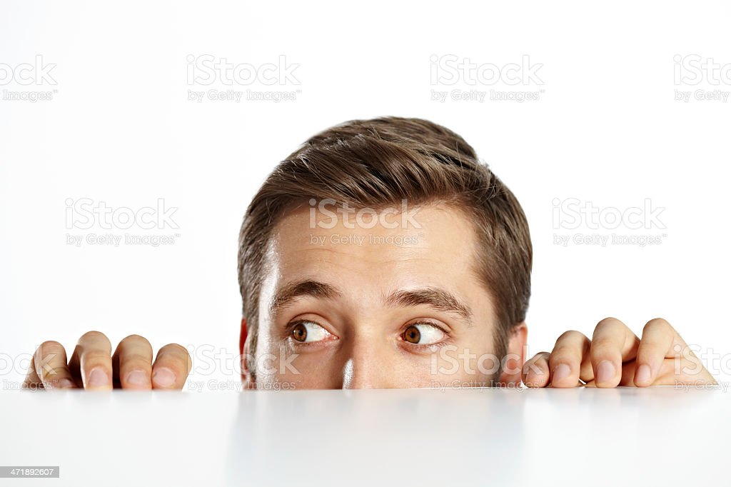 Curious man looking over a table. stock photo