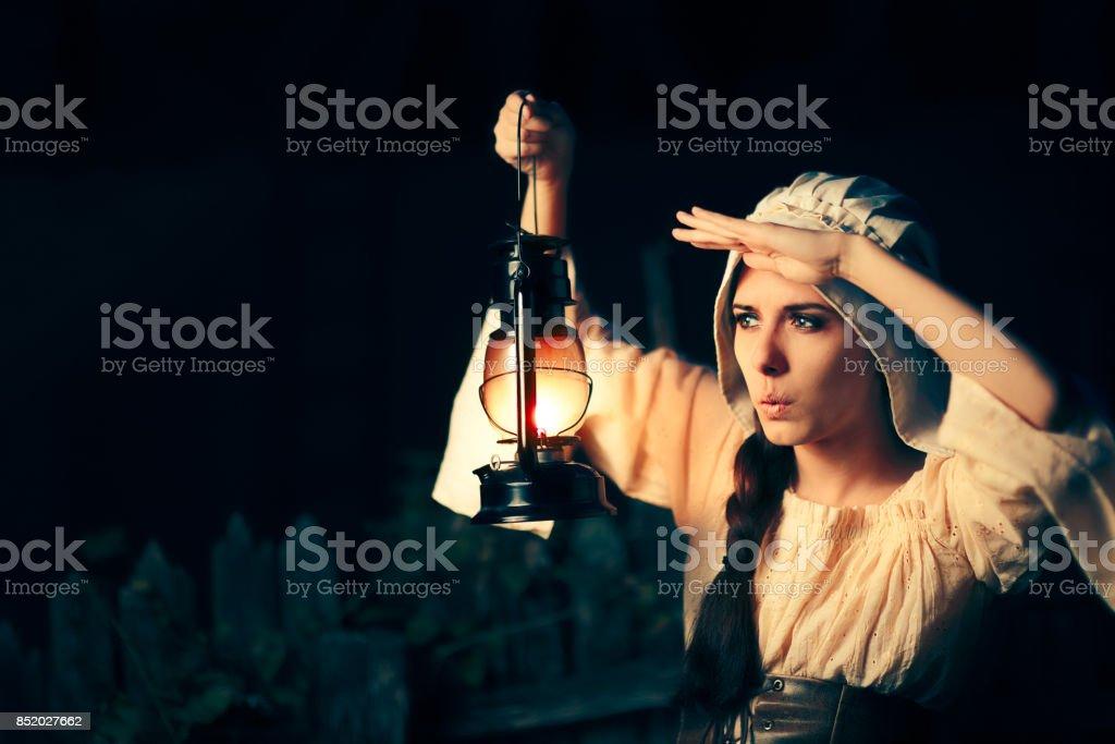 d7cf5fde6 Mulher Medieval curiosa com lanterna Vintage fora à noite foto royalty-free