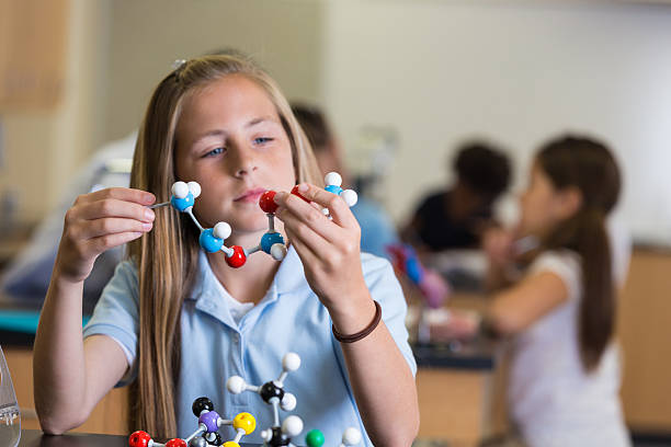 Curioso estudante de ensino médio usando o átomo modelo durante a aula de Ciências - foto de acervo