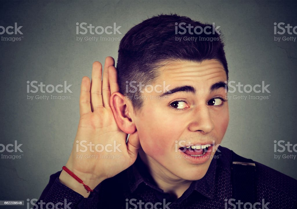 Curious nosy man with hand to ear carefully secretly listening royalty-free stock photo