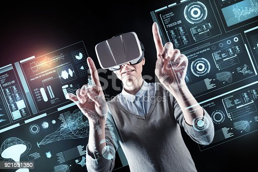 istock Curious person pointing to the screen while wearing virtual reality glasses 921591380