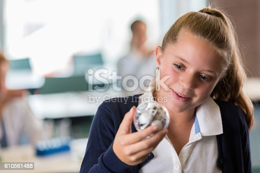 istock Curious preteen girl looking at robot in STEM class 610561488