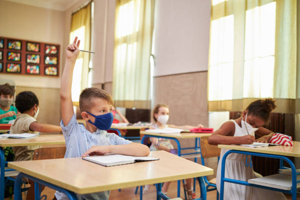 Curious school boy raise his hand to ask a teacher about subject he don't understand stock photo