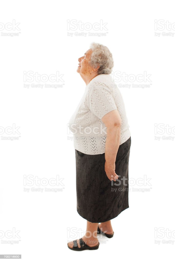 Curious senior woman standing looking up stock photo