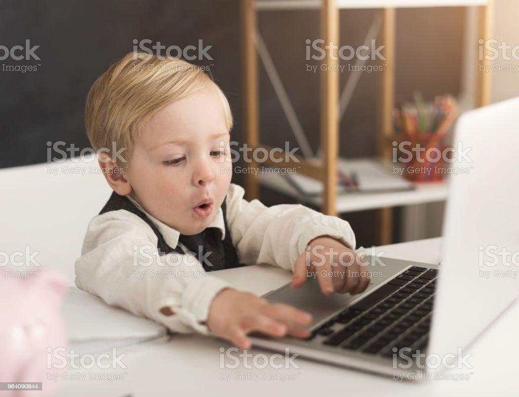 ノート パソコンとテーブルで形式的に好奇心の小さなビジネスマン - めがねのロイヤリティフリーストックフォト
