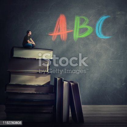 istock Curious student guy seated on the top of a huge atack of books looking at the blackboard with ABC letters written 1152260605