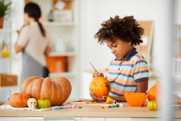 Curious talented boy with Afro hairstyle standing at counter with art and craft tools and painting pumpkin with paintbrush Curious talented boy with Afro hairstyle standing at counter with art and craft tools and painting pumpkin with paintbrush carving craft activity stock pictures, royalty-free photos & images