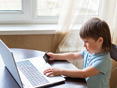 istock Curious toddler boy explores the laptop and presses buttons on computer keyboard. Kid holds credit card in hand. Puzzled child. 1217168667