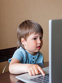 istock Curious toddler boy explores the laptop and presses buttons on computer keyboard. 1217168369