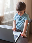 istock Curious toddler boy explores the laptop and presses buttons on computer keyboard. 1217168440