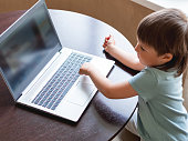 istock Curious toddler boy explores the laptop and presses buttons on computer keyboard. 1217168578
