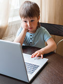 istock Curious toddler boy explores the laptop and presses buttons on computer keyboard. 1217168707