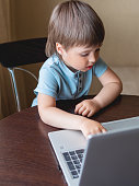 istock Curious toddler boy explores the laptop and presses buttons on computer keyboard. 1217169254
