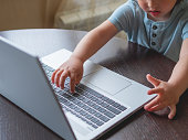 istock Curious toddler boy explores the laptop and presses buttons on computer keyboard. 1217856405