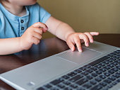 istock Curious toddler boy explores the laptop and presses buttons on computer keyboard. 1217964159