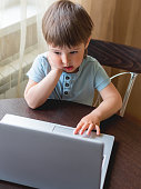istock Curious toddler boy explores the laptop and presses buttons on computer keyboard. 1219563024