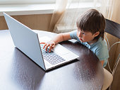 istock Curious toddler boy explores the laptop and presses buttons on computer keyboard. 1249246671