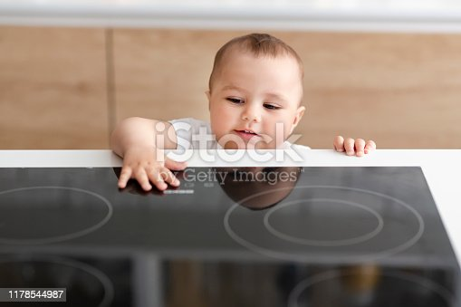 istock Curious toddler reaching hand to hot electric cooktop 1178544987