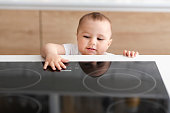 Hazard at kitchen. Curious toddler reaching hand to hot electric cooktop, free space