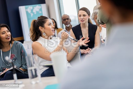 Mid adult Hispanic businesswoman gestures while asking a question during a Q&A portion of a business conference. She is speaking into a microphone.