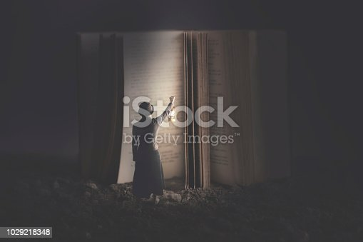 istock Curious woman illuminates with a lantern a giant book at night 1029218348
