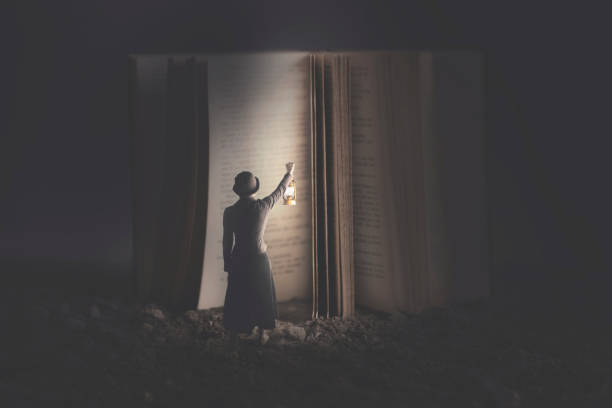 Curious woman illuminates with a lantern a giant book at night stock photo