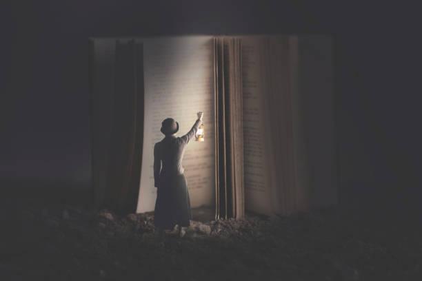 Neugierige Frau beleuchtet mit einer Laterne ein riesiges Buch in der Nacht – Foto