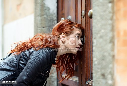 side view of curious woman looking on keyhole, red hair, leather jacket.