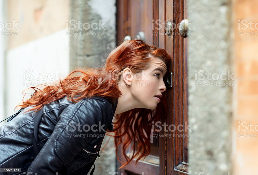 curious woman looking on keyhole stock photo