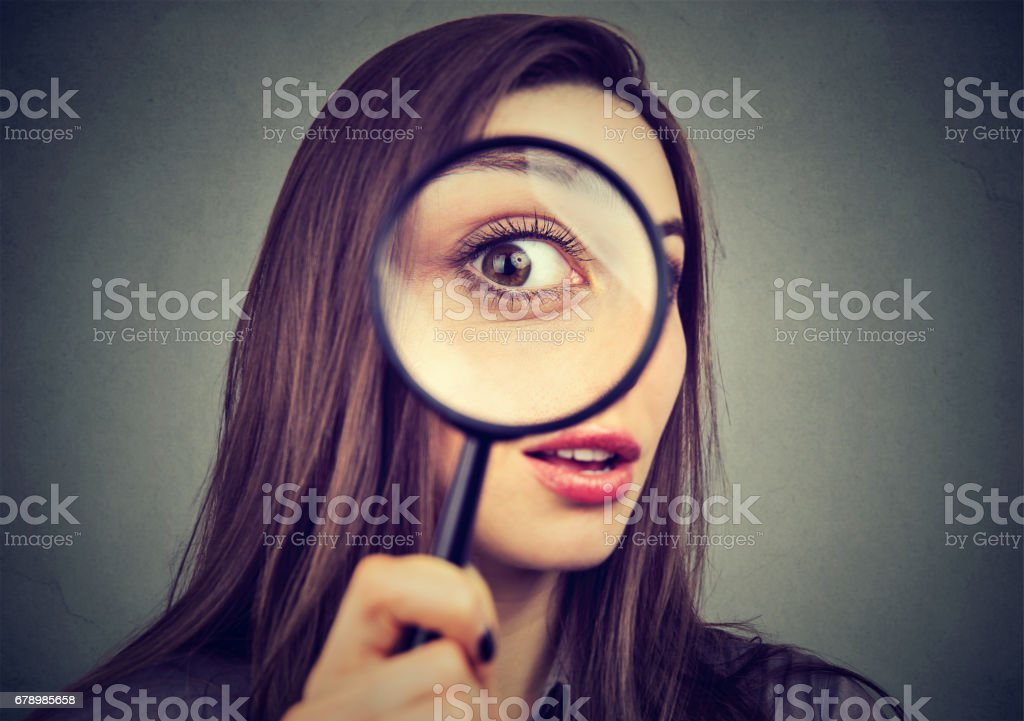 Curious woman looking through a magnifying glass stock photo