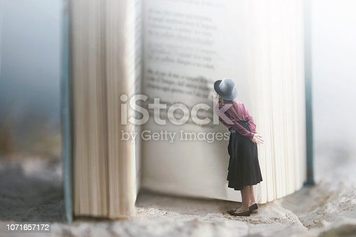 istock Curious woman reads a giant book 1071657172