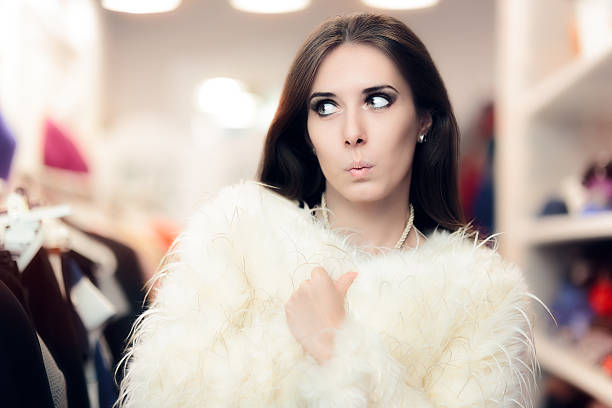 Curious Woman Wearing White Fur Coat in Fashion Store stock photo