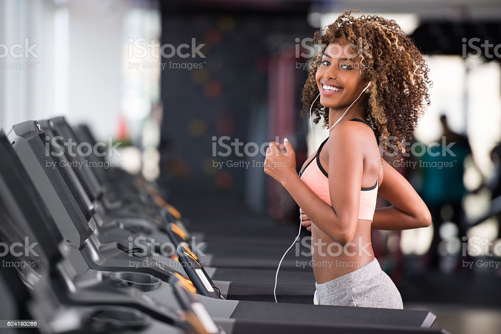 Curled hair woman training at fitness club. stock photo